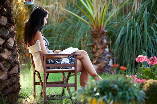 Young woman reading book surrounded by tropical plants