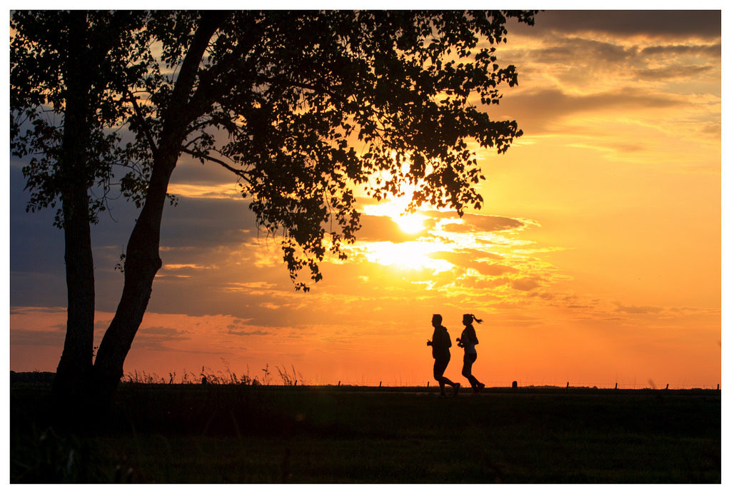 Two people running together in front of sunset