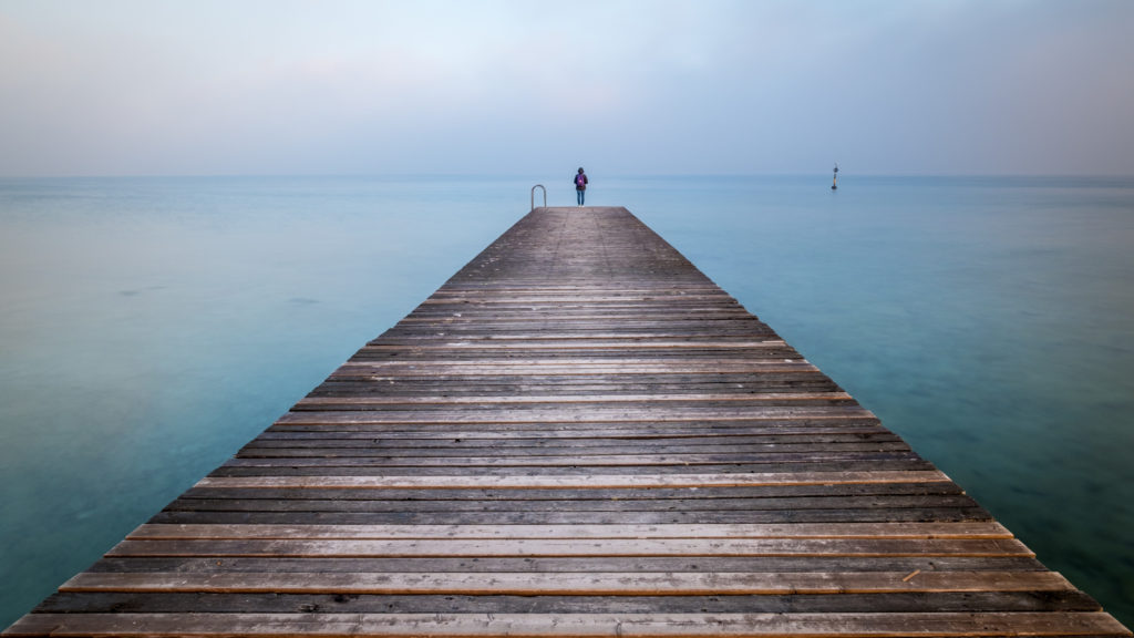 Lone person standing at end of pier over ocean