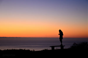 Woman standing on bench by ocean at sunset