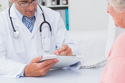 doctor writing prescription for older lady