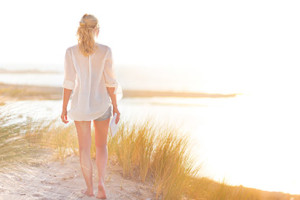 young lady walking along beach at sunrise