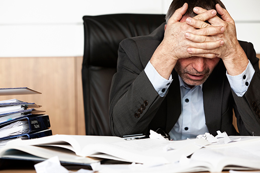 An executive stressed by piles of work