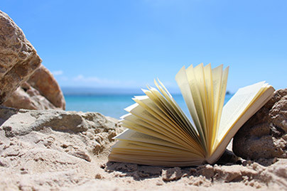 An open book laying on a rock in front of the ocean