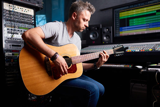 A musician playing guitar in a recording studio