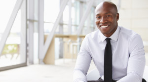 professional businessman sitting and smiling at camera