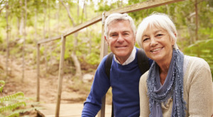 older man and woman sitting in the woods smiling at camera