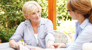 younger professional care support talking with older lady