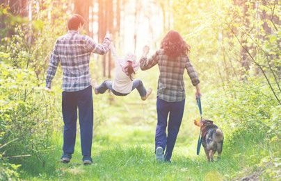 family walking together in the woods with dog