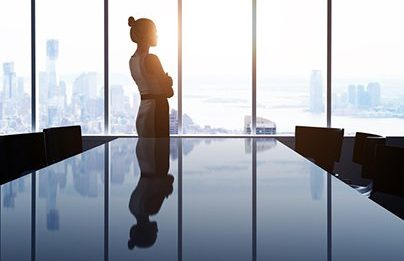 woman in office building overlooking skyline