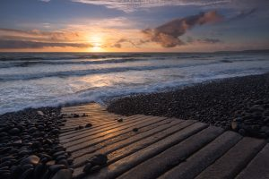 rocky pathway leading to the ocean at sunset