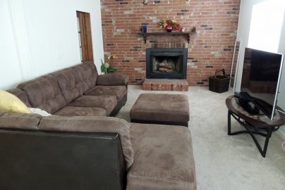 inside common area with couches, fireplace, and a tv