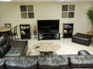 Common area with leather couches, table, and TV