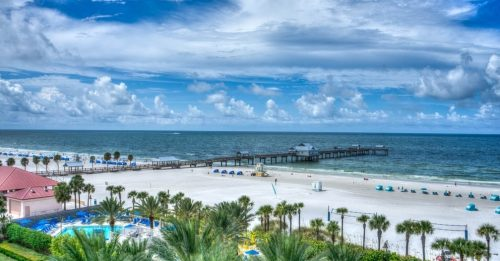 A clearwater beach with palm trees, a pool, and a blue sky